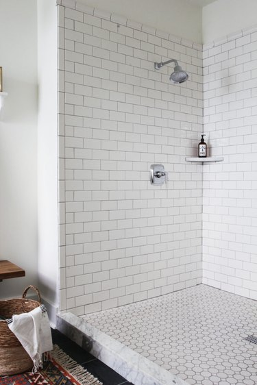 Polished chrome shower fixtures in subway tile with dark grout