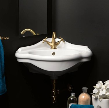 White wall mount corner bathroom sink with brass faucet in black bathroom