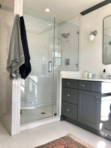 Polished chrome shower fixtures and hardware in gray and white bathroom