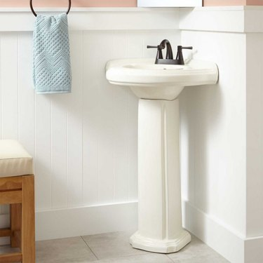 Classic white corner bathroom sink with black faucet in pink and white bathroom