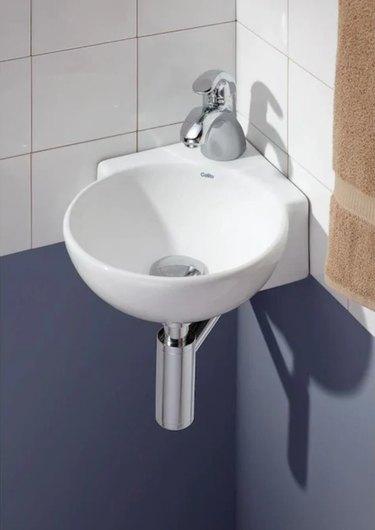 Semi-circle wall mount corner bathroom sink against white tile backsplash