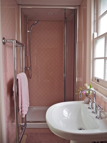 Polished chrome shower fixtures in pink tile shower
