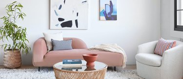 Small Space Daybed Ideas with Pink daybed, white chair, coffee table, plant, art, pottery.
