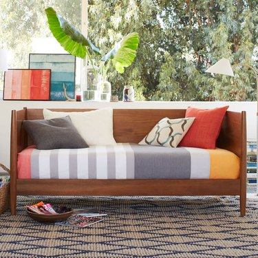Small Space Daybed Ideas with Wood daybed, striped blanket, pillows, rug, plants, art, window.