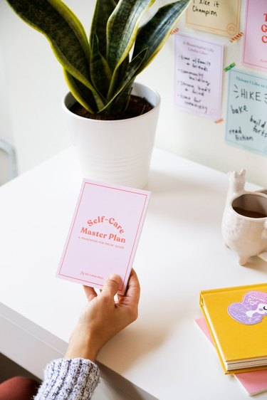 hand holding pink journal over white desk with plant