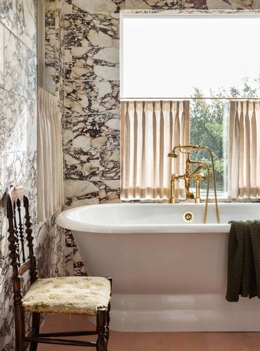 sophisticated bathroom with cafe curtains and brass bath fixtures