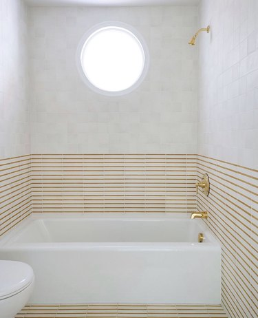 mustard striped tile with brass shower and tub fixtures