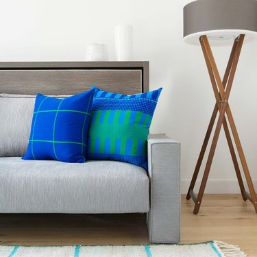 blue and green patterned throw pillows on gray sofa