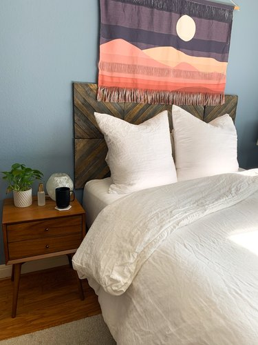 Bedroom with blue walls, wooden headboard, nightstand, and white bedding.