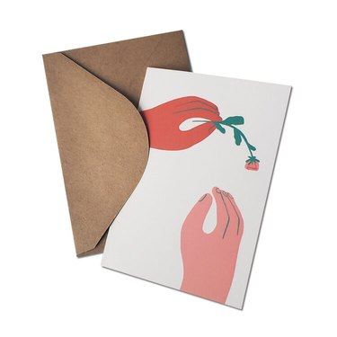 card with one hand giving a flower to another hand