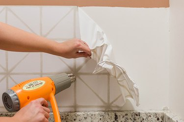 Peel the wallpaper back at a 45-degree angle to remove it from the wall.