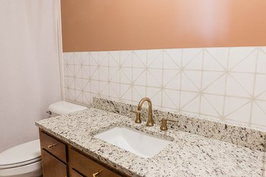 Remove everything from the wall that has the peel-and-stick wallpaper on it.
