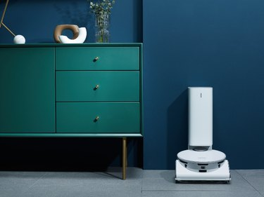 dark green dresser with high-tech vacuum next to it
