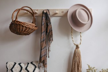 DIY wooden peg rail on wall with baskets, scarf and hat hanging from it