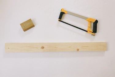 1x4 wood board cut with hacksaw next to sanding sponge