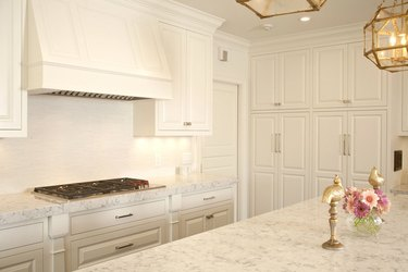 all white kitchen with marble countertops and raised panel cabinetry