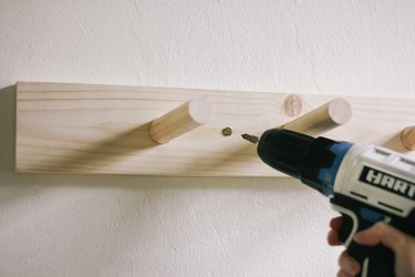 Drilling screw through peg rail and into wall