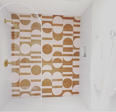 yellow and pink graphic wall tile with brass shower fixtures