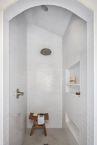 modern shower fixtures with white subway tiled walls and a wooden stool in the corner