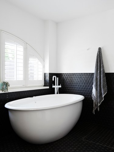 modern bath fixtures with white freestanding tub and black tile