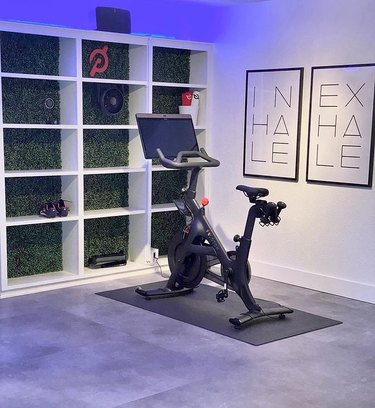 peloton bike in workout room with white bookshelf and black fan