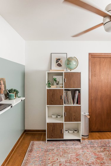 Midcentury modern home office with green and white walls and a modern shelf