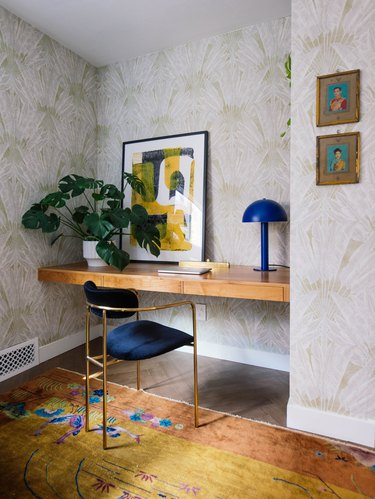 Midcentury modern home office with blue velvet chair and modern blue desk lamp
