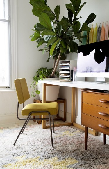 Midcentury modern home office with vintage yellow chair and fiddle leaf fig