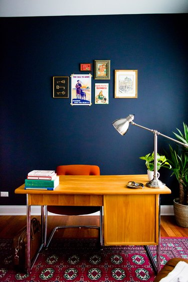 Midcentury modern home office with navy walls and small gallery wall
