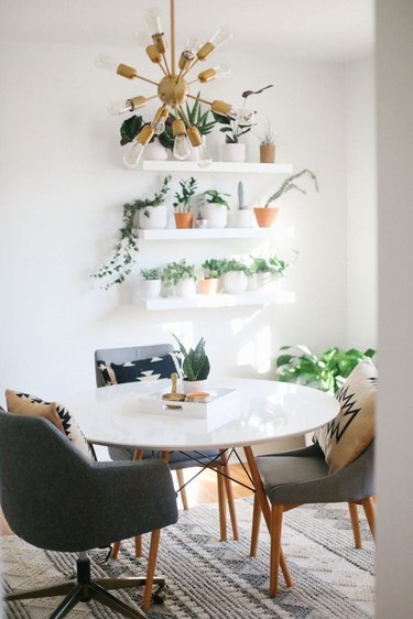 Midcentury modern home office with white open shelves, plants, and large table
