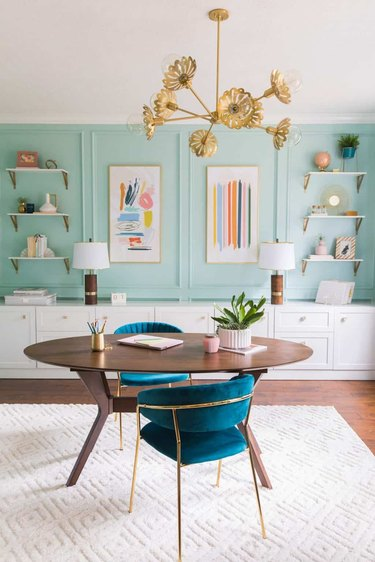 Midcentury modern home office with mint green walls and brass chandelier