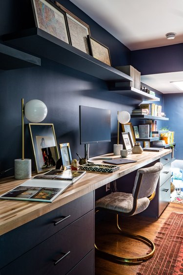 Midcentury modern home office with blue walls and midcentury desk lamps