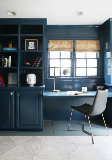 Midcentury modern home office in navy blue with built-in displaying decor