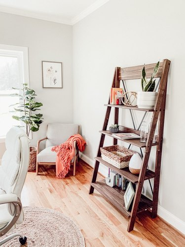 Farmhouse home office with ladder shelf and chair in corner with orange blanket