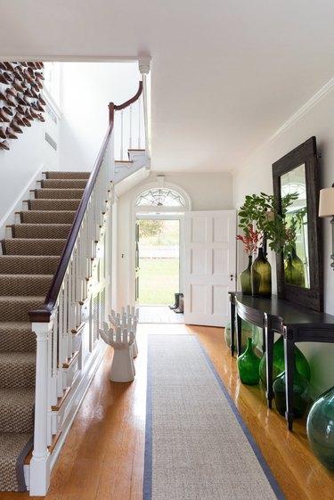 Hallway Runner Ideas in Entryway with jute runner, credenza, mirror, art, plants, stairs, front door.
