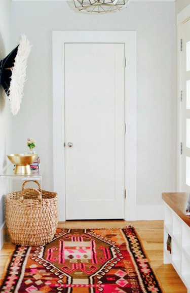 Hallway Runner Ideas in Entryway, basket, rug, wood floors, white walls, acrylic credenza.