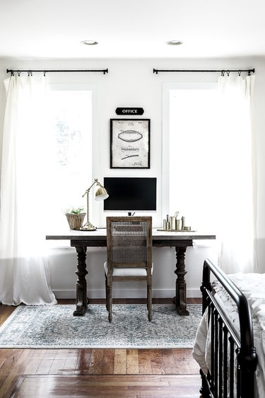 Farmhouse home office in bedroom with wood desk and wall art