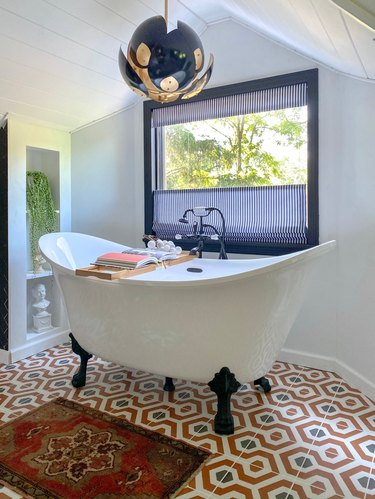 Industrial tub filler with clawfoot tub and modern light fixture