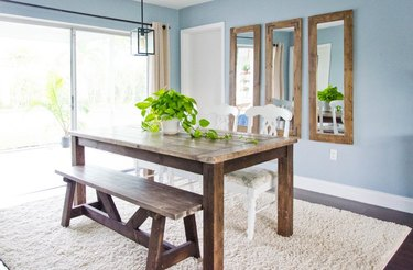 farmhouse style dining table in room with blue walls and mirrors