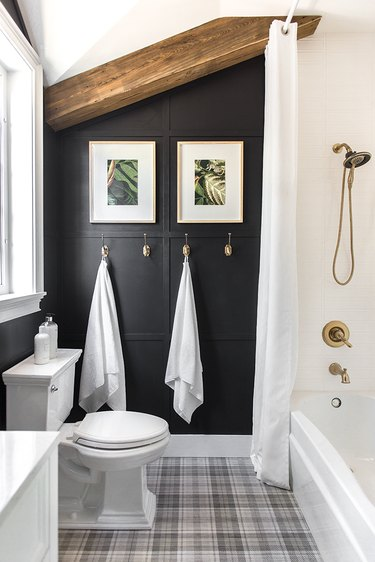 Brass plumbing fixtures in white shower with black wall in bathroom