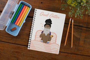 """writing tools and notebook with illustrator and text that reads """"goal getter"""""""