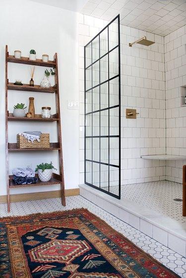 Brass rain showerhead with white tile surround in modern industrial bathroom