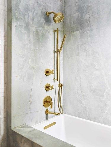 Brass plumbing fixtures in emerald quartz shower