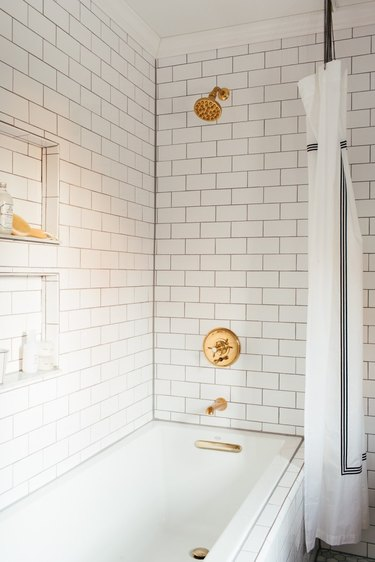 Brass plumbing fixtures with white subway tile shower