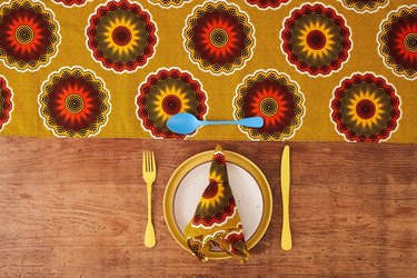 printed table runner, utensils, plate, and patterned cloth napkin