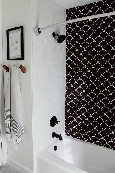 Black plumbing fixtures with black fish scale tile shower wall