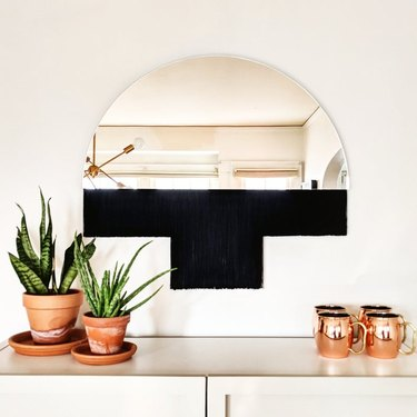 mirror with black fringe near plants and cups