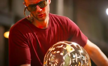 person blowing glass