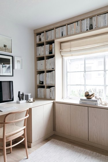 white modern, Scandinavian home office surrounded by light wood built-ins
