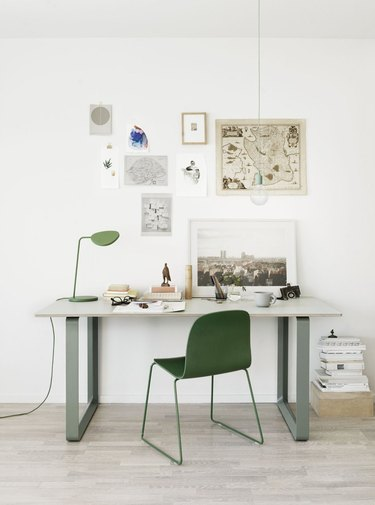 white Scandinavian home office with sage green and white desk, green chair and art on the walls